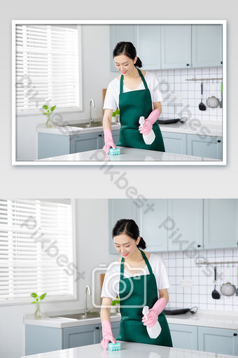 Young female housekeeping service housewife wiping table in kitchen Photo Template JPG